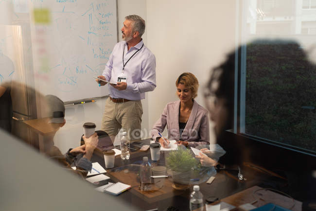 Executive giving presentation on whiteboard in office — Stock Photo