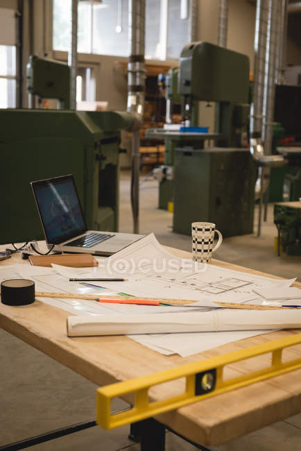 Blueprints with laptop and instruments on table in workshop — Stock Photo