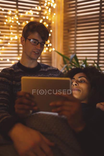 Paar nutzt digitales Tablet im Wohnzimmer mit Lichterglanz zu Hause — Stockfoto