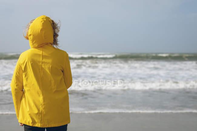 Vista posteriore della donna in giacca gialla in piedi in spiaggia . — Foto stock