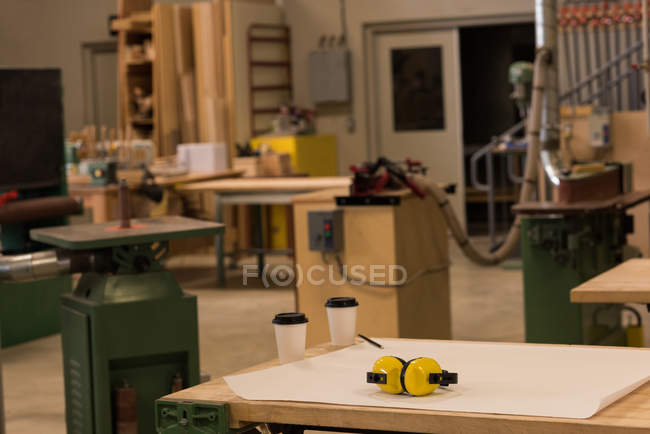 Blueprint with earmuffs and disposable cups on table in workshop — Stock Photo