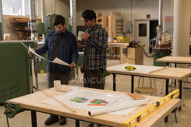 Two craftsmen discussing over blueprint in workshop — Stock Photo