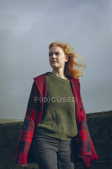 Femme rousse bien pensés, marchant dans la plage de vent. — Photo de stock
