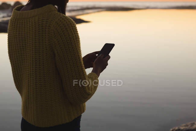 Mid section of woman using mobile phone on beach during sunset — Stock Photo