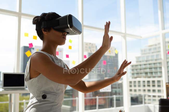 Vista lateral del ejecutivo empresarial utilizando auriculares de realidad virtual en la oficina . - foto de stock
