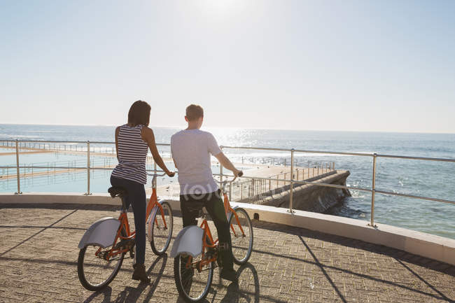 Couple with bicycles standing on promenade near beach — Stock Photo