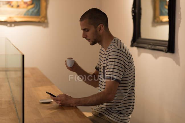 Человек, с помощью мобильного телефона имея кофе в кафе — стоковое фото