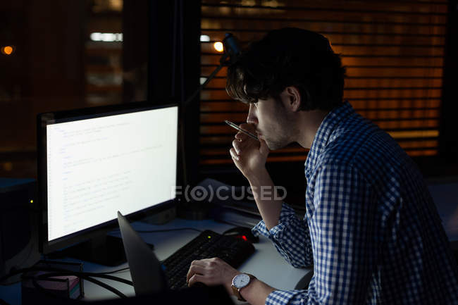 Thoughtful male executive using desktop pc in office at night — Stock Photo