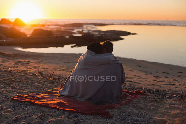 Couple romancing on beach during sunset — Stock Photo