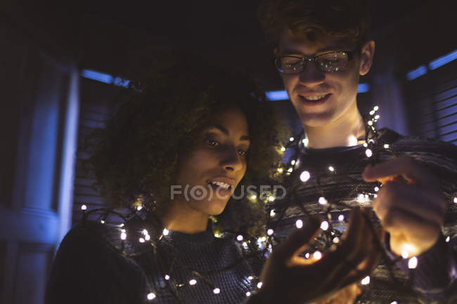 Happy couple playing with fairy lights at home — Stock Photo