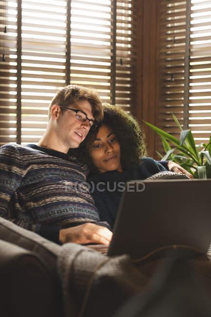 Coppia utilizzando il computer portatile in soggiorno a casa — Foto stock