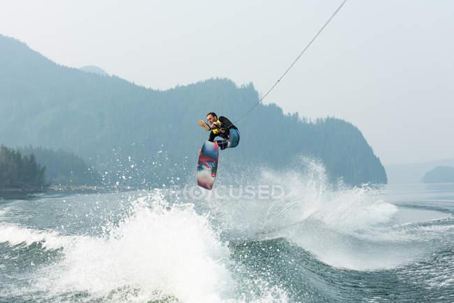 Masculino wakeboarder surfando ondas de rio da floresta — Fotografia de Stock