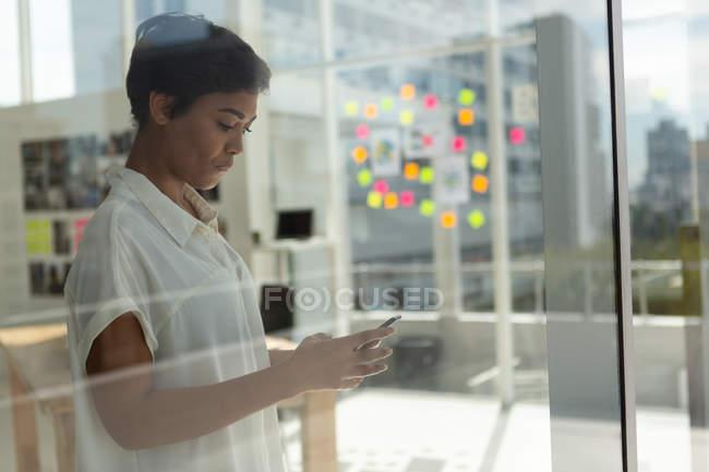 Вид сбоку бизнеса исполнительной власти с помощью мобильного телефона в офисе. — стоковое фото
