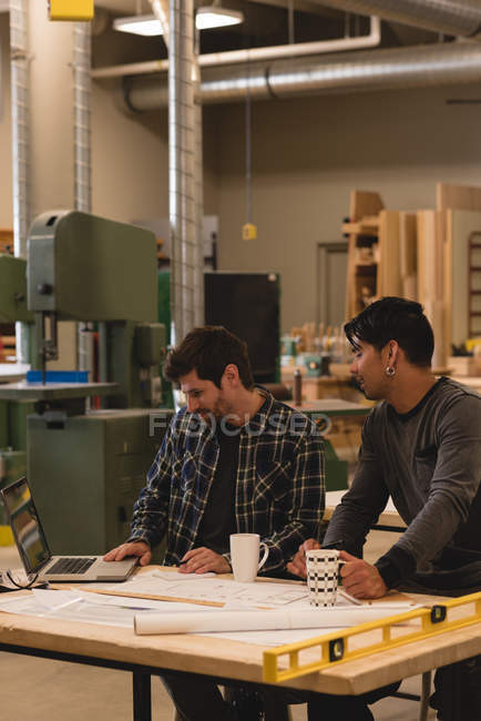 Two attentive craftsmen using laptop in workshop — Stock Photo