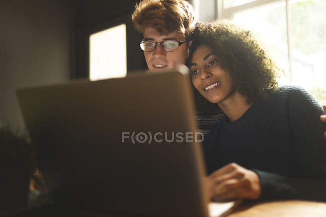 Young couple using laptop at home — Stock Photo