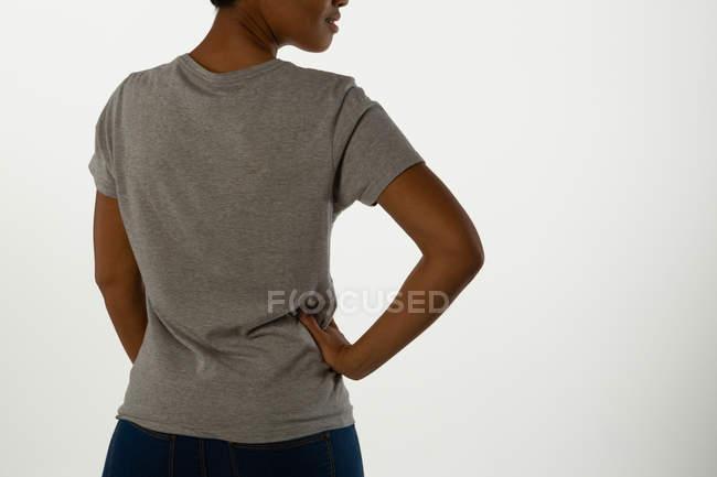 Vista trasera de la mujer casual posando sobre fondo blanco . - foto de stock