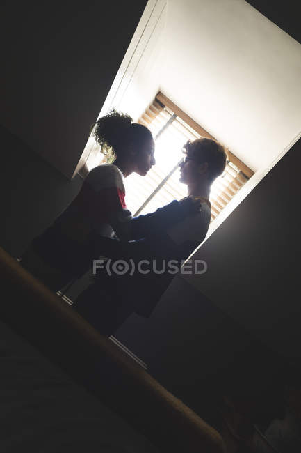 Young couple romancing at home in backlit — Stock Photo