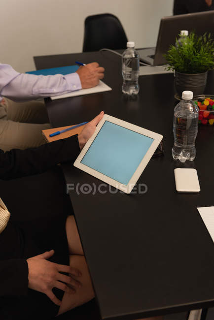 Female executive holding digital tablet in office — Stock Photo