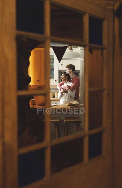 Coppia che si abbraccia in cucina a casa — Foto stock