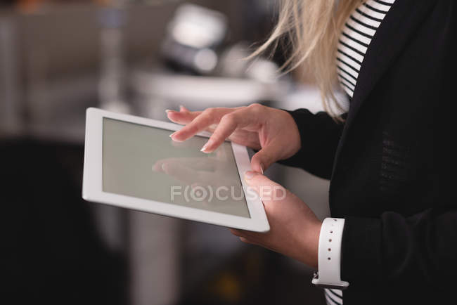 Mid section of woman using digital tablet indoors — Stock Photo