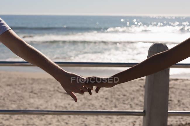 Пара держащихся за руки на набережной возле пляжа — стоковое фото