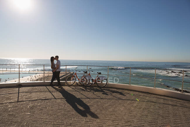 Romántica pareja besándose en el paseo marítimo cerca de la playa - foto de stock