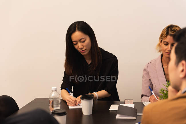 Female executive writing on notepad in office — Stock Photo