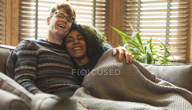 Couple relaxing under blanket in living room at home — Stock Photo