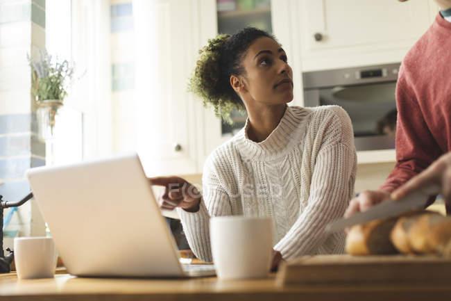 Frau benutzt Laptop, während Mann in Küche zu Hause Laib Brot schneidet — Stockfoto