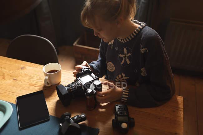 Donna che rivede le foto sulla fotocamera a casa — Foto stock
