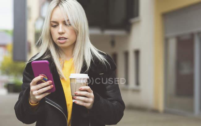 Женщина пользуется мобильным телефоном во время кофе — стоковое фото