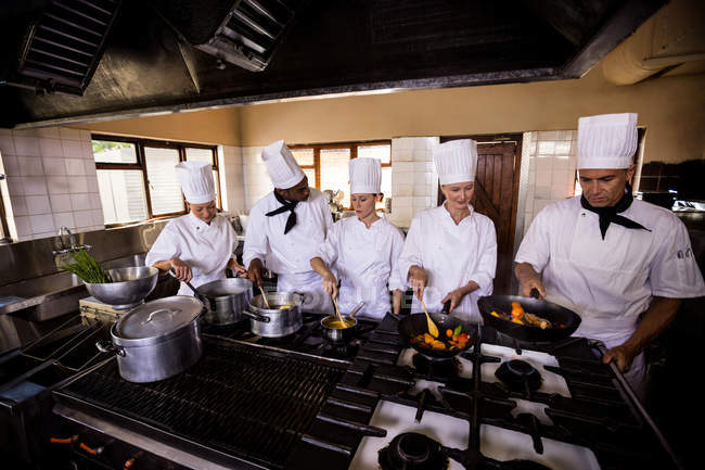 Group of chef preparing food in kitchen — Stock Photo