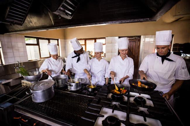Gruppo di chef che prepara il cibo in cucina — Foto stock