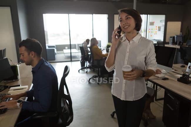 Женщина-руководитель разговаривает по мобильному телефону в офисе — стоковое фото