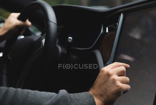 Gros plan de l'homme à l'aide de carte navigateur pendant que vous conduisez une voiture — Photo de stock