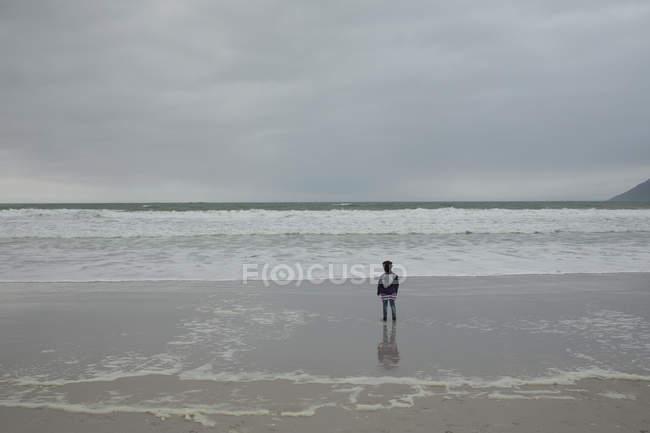 Вид сзади на девушку, стоящую на пляже — стоковое фото