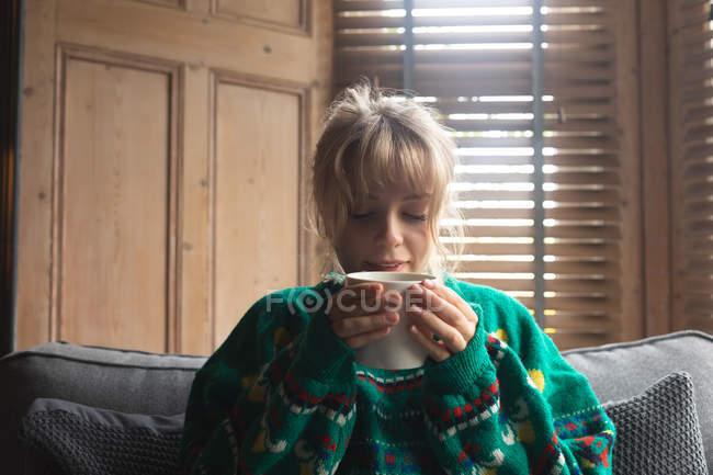 Женщина пьет кофе, сидя дома на диване — стоковое фото