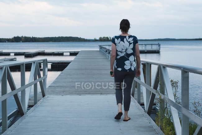 Vista posteriore della donna che cammina sul molo — Foto stock