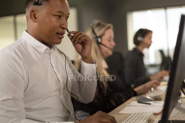 Руководители службы клиента говорить на гарнитуре на стол в офисе — стоковое фото