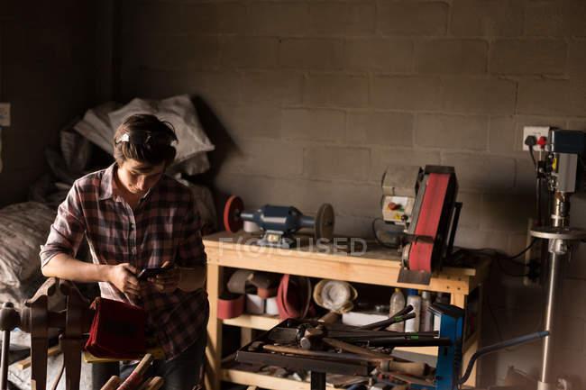 Metalsmith feminino usando telefone celular na fábrica — Fotografia de Stock