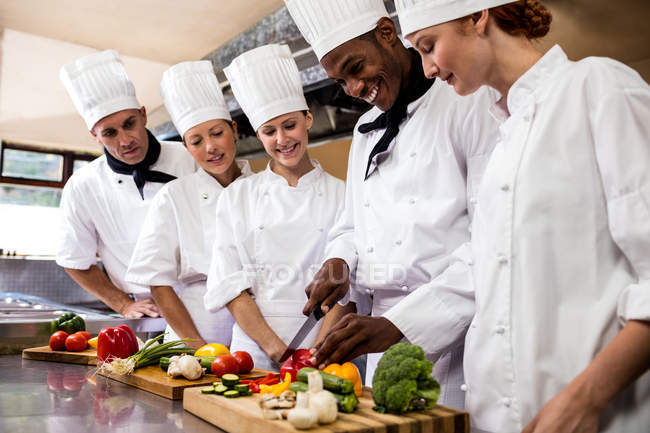 Head chef teaching his team to chopping vegetable in kitchen — Stock Photo