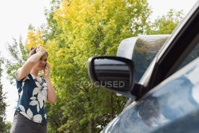 Mujer hablando en el teléfono móvil durante la avería del coche en un día soleado - foto de stock