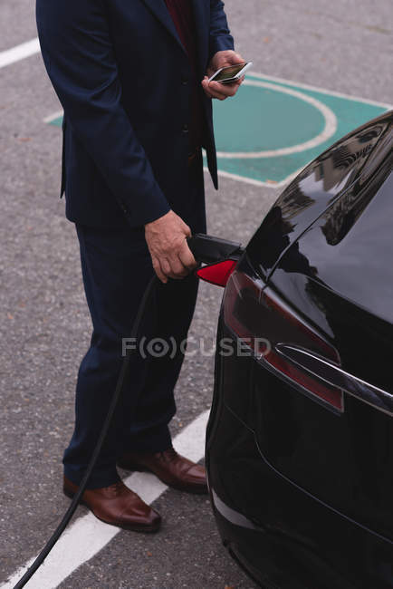 Niedriger Anteil der Geschäftsleute nutzt Handy beim Laden von Elektroautos — Stockfoto