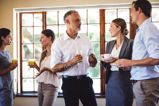 Business people interacting while having food and drink in restaurant — Stock Photo