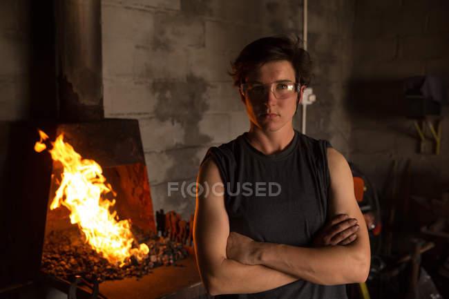 Портрет женщины metalsmith стоя с оружием перешли на фабрике — стоковое фото
