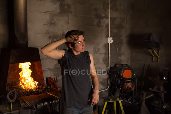 Young female metalsmith standing in factory — Stock Photo