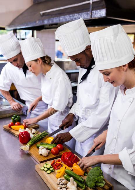 Grupo de chef picando verduras en la cocina - foto de stock