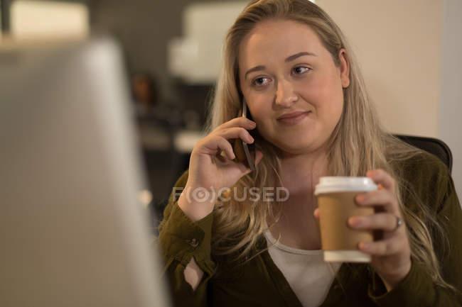Исполнительный говорить на мобильном телефоне имея кофе в офис — стоковое фото