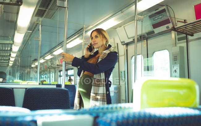 Side view of pregnant woman talking on mobile while travelling in train — Stock Photo