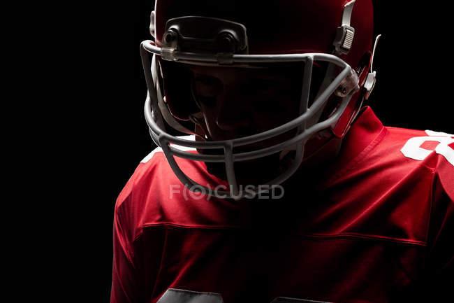 Крупный план американского футболиста, стоящего в регби-шлеме — стоковое фото